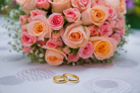 Bridal bouquet with orange and pink roses of different size with handle on white background.