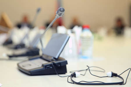 Soft focus of wireless Conference microphones and notebook in a meeting room. Before a conference, the microphones in front of empty chairs