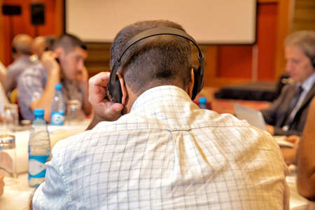 People using ear headphones for translation during event and meeting Banque d'images