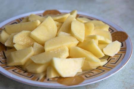 Chopped potatoes. In the chopped potato plate . Sliced, peeled raw potatoes on a board . Chopped potatoes in a bowl . Diced potatoes - as an ingredient to a potato based dish