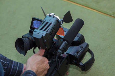 Covering an event with a video camera., Videographer takes video camera with free copy space for text., Video camera operator working with his equipment., close up of television operator with camera. 版權商用圖片