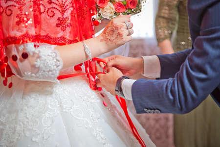 Close the ribbon on the belly of the bride . Lose the ribbon on the belly of the bride . Wedding . Bridesmaids lace bride Foto de archivo