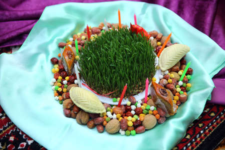 Novruz concept plate of traditional Azerbaijan pastries packlava and shekerbura in copper vintage tray with wheat grass semeni on white wooden table background,