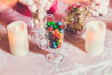 Dulces multicolores. Caramelos de colores en un vaso. El chocolate redondo es muy colorido. Foto de archivo