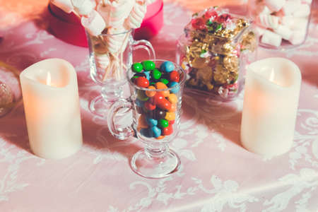 Wielokolorowe słodycze. Kolorowe cukierki w szklance. Okrągła czekolada jest bardzo kolorowa Zdjęcie Seryjne