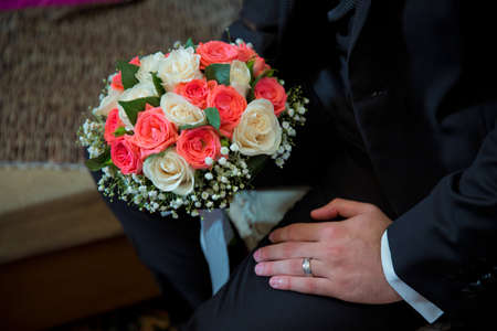 Groom holding wedding bouquet of white roses . bridal bouquet bride and groom on the Azerbaijan wedding . holding a beautiful bouquet of tender and colorful flowers tied with a pretty ribbon