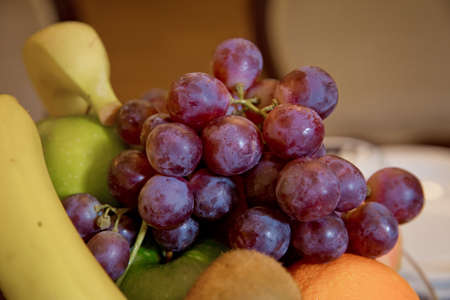 Red grapes on fruit in the plate.Fresh red grapes on a reflecting plate. Wet fruits, partial with mirror image, slightly blurred. Bright clear colors. Space for text. selective focus. Banque d'images - 122342051