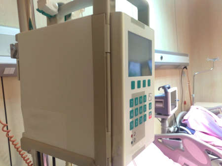 Infusion pump in the hospital . Automatic infusion pump . Saline solution controller in hospital . Infusion pump drip for patients in the hospital . Modern and comfortable equipped hospital room . Stock Photo