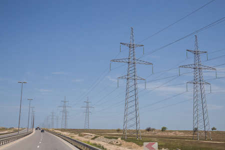 Electricity transmission power lines High voltage tower . Power line high voltage post with blue sky background . Electricity pylon on nature background . Road Stock fotó