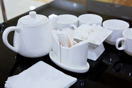 Plasterboard, cutlery, toothbrush, teapot, napkin on a black glass table. Catering - rows of cups served for tea table 版權商用圖片