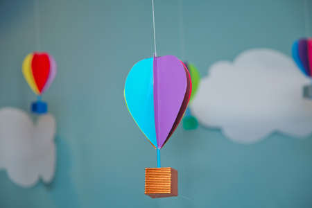 Hanging from above Colorful paper balloon with blue sky background and clouds. Origami made colorful air balloon cloud. Beautiful colored paper lanterns hanging on the ceiling as air balloons
