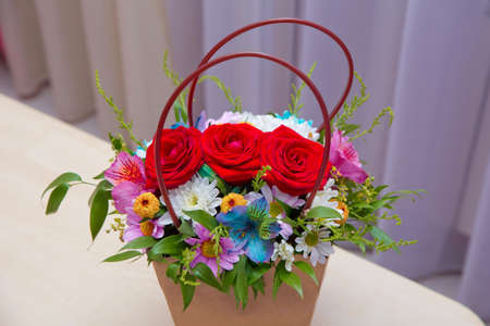 Paper bouquet of fresh red, white , blue, purple roses . Paper bouquet of multicolored roses . Pink, red flower picture close up in the bouquet.