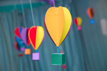Hanging from above Colorful paper balloon with blue sky background and clouds. Origami made colorful air balloon cloud. 版權商用圖片