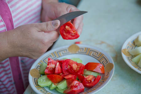 Tomatoes cut into cucumbers with female knives. Women make salad .Dieting, healthy food, weight losing, well-being. Overweight fat woman slicing a tomato for salad.