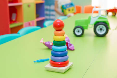 Educational toys for toddlers, gripping rings, isolated on yellow. Toy for babies and toddlers to joyfully learn mechanical skills and colors Stock Photo - 128832635