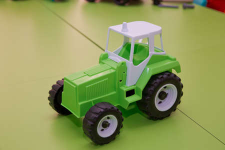 Green Tractor. Toy for children. Toy tractor on green background. Stock fotó