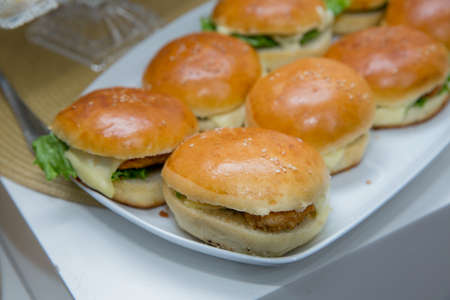Mini or Small Burger Canape in Luxury Restaurant for Brunch Time . Beautifully decorated catering banquet table with different hamburgers burgers sandwiches on a plate on corporate birthday