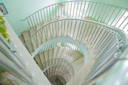 Spiraling steps . Circular Staircase. Spiral staircase from bottom view with white cement wall Spiral staircase in Lighthouse in Baku.