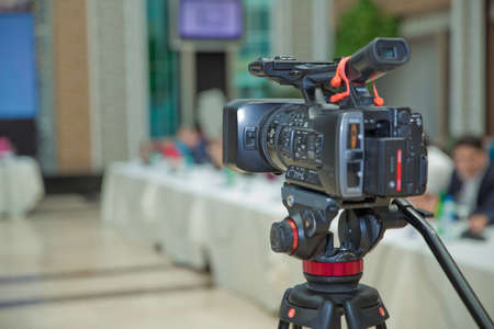 The rear view of the video camera is standing on the tripod and recording the live meeting event with the audience . The rear view of the video recorder is recording the live event .