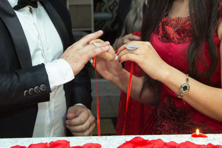 Engagement rings and hands of bride and groom. young engagement couple at ceremony. matrimony. man and woman in love. two happy people celebrating becoming family . the groom dresses a ring on a finger