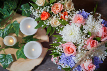 Multi-colored flower bouquet, candles in the background. White , Pink roses, purple and candles on white candles background. Selective focus.