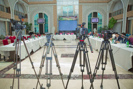 The rear view of the video camera is standing on the tripod and recording the live meeting event with the audience . The rear view of the video recorder is recording the live event . Stock Photo - 128832772