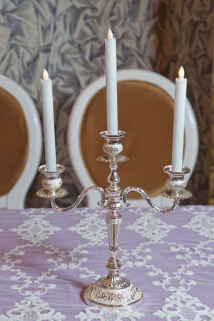 Three white candles on the table . three arms candle stick holder, two candelabra atop, on top of furniture, table against white wall in living room, house, home bedroom