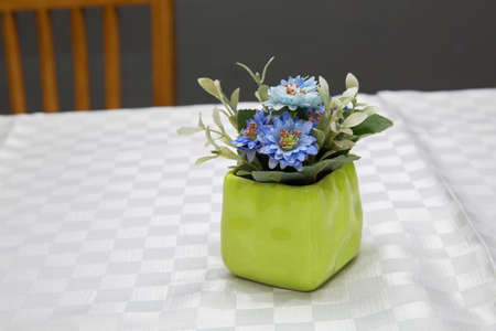Green Pot with artificial purple daisy flower. Purple primroses in spring blooming in a green pot on a white background announce spring and warm weather