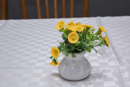 Clay Pot with artificial yellow daisy flowers. Yellow primroses in spring blooming in a white pot on a white background announce spring and warm weather