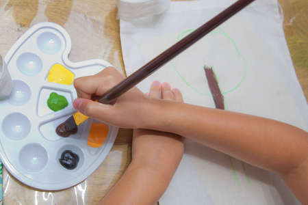 Top view childs hands draws a gouache on paper. Gouache and paper for painting and child drawing. Kid hands painting at the table with art supplies, top view