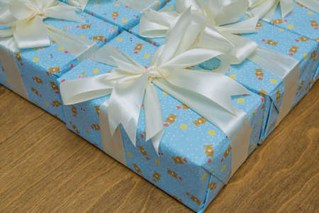 Blue gift boxs with a white ribbon and bow . Gift, isolated on wooden background .Group of blue gift boxes with silver ribbons isolated on white background with clipping path Imagens - 128832965