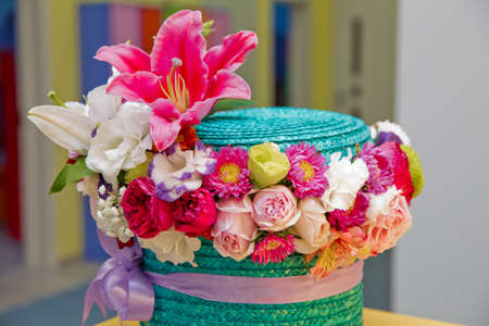 Colorfull Flower arrangement in a hat box , a pot of cyan for a girl on a gift with roses . Multi-colored flower cyan bouquet . Flowers bouquet made of scarlet red, white, pink roses . Purple ribbon