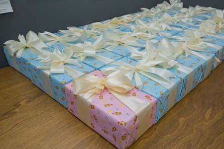 Pink and blue gift boxs with a white ribbon and bow . Gift, isolated on wooden background .Group of Pink and blue gift boxes with silver ribbons isolated on white background with clipping path Imagens - 128832987