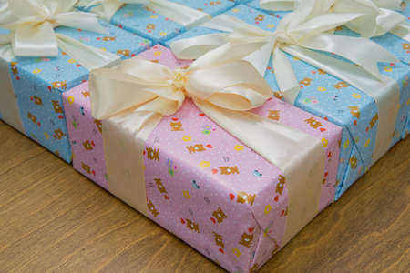 Pink and blue gift boxs with a white ribbon and bow . Gift, isolated on wooden background .Group of Pink and blue gift boxes with silver ribbons isolated on white background with clipping path Imagens - 128832984