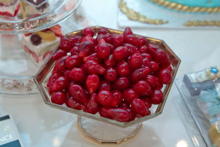 Ripe dogwood in a glass plate .Fresh dogwood in a plate on a white table