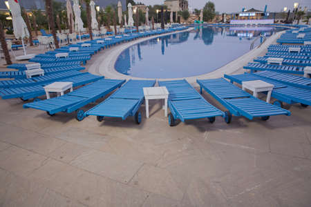 Empty sunbeds by the beautiful resort pool . Lounge sunbeds near swimming pool .Sun loungers by the pool, blue, comfortable atmosphere .Swimming pool beds in nature. Stockfoto