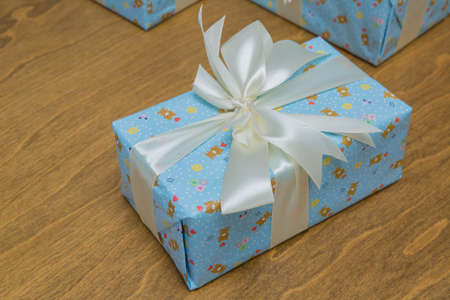Blue gift boxs with a white ribbon and bow . Gift, isolated on wooden background .Group of blue gift boxes with silver ribbons isolated on white background with clipping path Imagens - 128833081