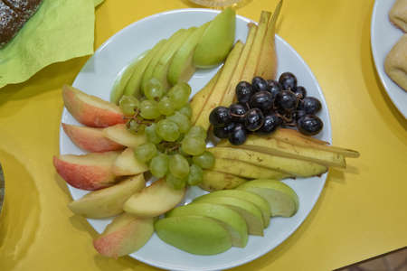Pickled apple and pear. Black and white grape in the plate . Chopped fruits . Black and white grape in the pot. Peeling and pear in the plate. White table grapes on a crystal plate