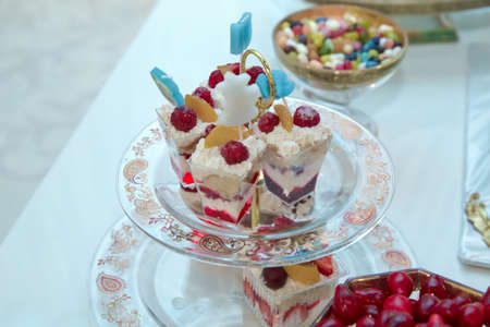 Meringue with summer berries and fruits. Meringue with strawberries, figs, raspberries and blueberries. Delicious desserts at wedding candy bar . top raspberry white cake Stock fotó