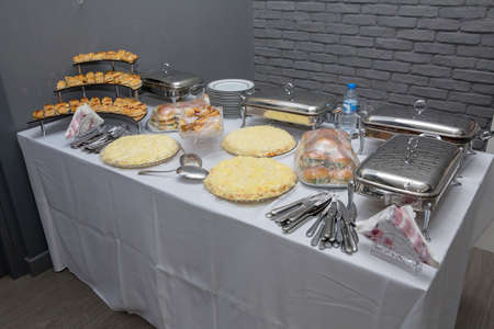 Pies with meat, cabbage or any filling. Baked pies in the oven. On a white plate and a peach color background. Fresh pies with meat, cabbage or any filling. Baked pies in the oven. Pies are in the pot
