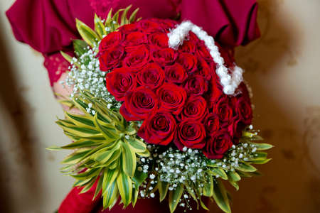 Big luxury bright bouquet in the hands of a cute girl. One hundred of garden red roses. Color passionately scarlet, Autumn mood. bouquet in a hat box . Henna . flower is a letter Z with white flowers
