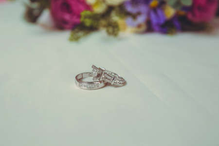 wedding rings and beautiful bouquet as bridal accessories . Beautiful toned picture with Engagement rings lie on a wooden surface against the background of a bouquet of flowers