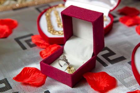 red ring box .Golden engagement ring in a heart shaped box and roses