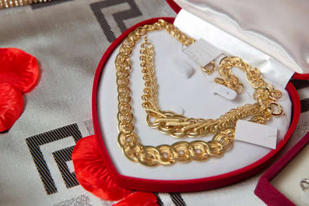 Gold necklace and ear rings and silver jewelry with pearls being placed and displayed in box with red velvet to be given as a gift to the bride .Gold necklace in a red box in the shape of a heaart Banco de Imagens