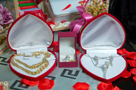 Gold necklace and ear rings and silver jewelry with pearls being placed and displayed in box with red velvet to be given as a gift to the bride .Gold necklace in a red box in the shape of a heaart Reklamní fotografie