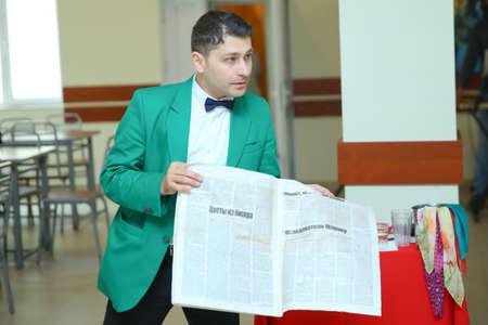 Magician with dove, Juggler man, Funny person, Black magic, Illusion . International Illusion Festival MAGIC 2018 A male magician shows a presentation with a newspaper