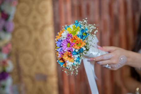 coloured macro photo of a detailed bouquet with colorfull roses, white small flowers and a fake diamond in the centre of the rose . He holds a wedding flower in his hand