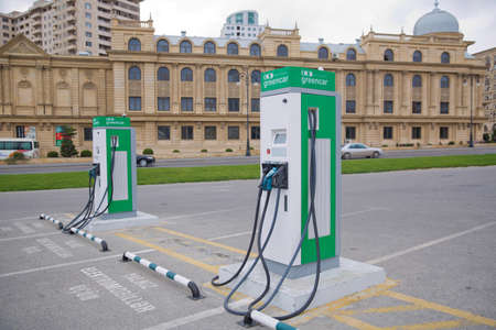 Electric car charger . The panel with two pistols for charging electric vehicles close-up. Electric charge station for eco car with charger to recharge electricity into vehicle on city street outdoor