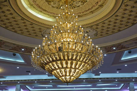 Close-up of a beautiful crystal chandelier . Gilded chandelier with burning candles in the Church. Large crystal chandelier in baroque style 版權商用圖片