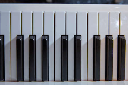 grand piano keyboard with glossy black and white keys as a music background in wide panoramic banner format, selected focus, narrow depth of field Фото со стока